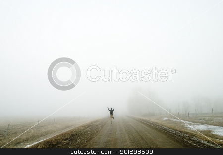 Jumping for Joy stock photo, Walking alone on a saskatchewan road in the fog, and jumping for joy. by Tyler Olson