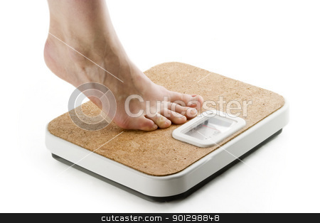 Weighing In stock photo, A female foot standing on tip toe, on a bathroom scale by Tyler Olson