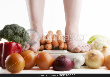 Healthy Choices stock photo, A pair of female feet standing on a bathroom scale with vegetables pilled around. by Tyler Olson