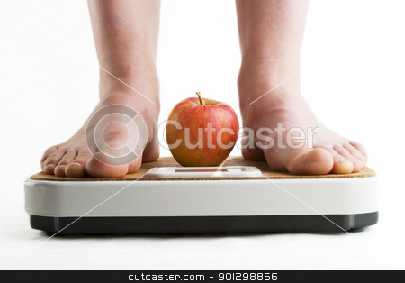 Weight Loss stock photo, A pair of female legs standing on a bathroom scale with an apple between them. by Tyler Olson