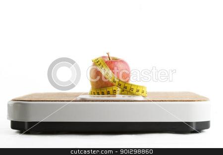 Healthy Choice stock photo, An apple on a bathroom scale with tape measure. by Tyler Olson