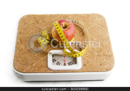 Healthy Choice stock photo, An apple on a bathroom scale with tape measure. by Tyler Olson