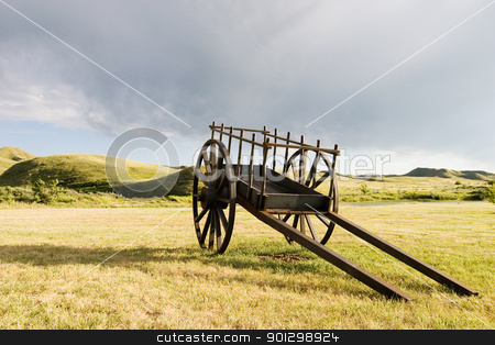 Old Wooden Cart stock photo, An old wooden cart sitting on the pairies by Tyler Olson
