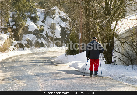 Winter Walk stock photo, An old man in Oslo, Norway walking on the road in winter with walking poles. by Tyler Olson