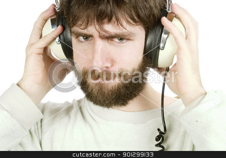 Sceptical Music stock photo, A young man looking sceptical while listening to music on headphones.  Isolated on white with clipping path. by Tyler Olson