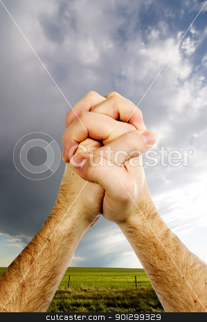 Praying Hands stock photo, A pair of hands praying with a prairie landscape with rain clouds in the background. by Tyler Olson