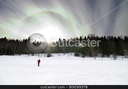 Skiing stock photo, Skiing on a contrasty dramatic day.  A winter landscape looking into the sun with lens flare. by Tyler Olson