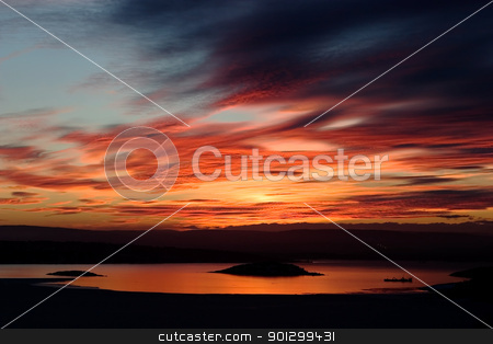Winter Fjord Sunset stock photo, A golden sunset going down behind a hill over a frozen lake - fjord.  Oslo fjord in March. by Tyler Olson