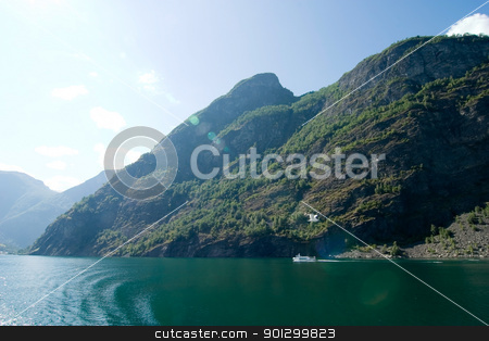 Aurlandsfjord stock photo, Fjord landscape in the western area of Norway, Aurlandsfjord in Sognefjord with sun flare and a ferry by Tyler Olson