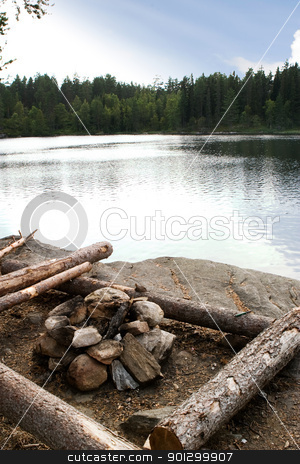 Campsite stock photo, A campsite by a lake in nature with a fire pit by Tyler Olson