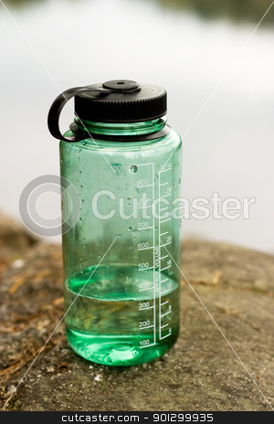 Waterbottle Outdoors stock photo, A green water bottle sitting in nature. by Tyler Olson