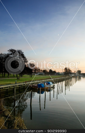 Harbor at Sunset stock photo, A boat harbor in the late fall painted in the evening light of sunset by Tyler Olson