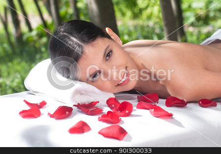 Portrait of woman on massage table stock photo, Portrait of a charming woman lying on a massage table in a health spa by Tyler Olson
