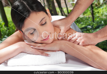 Attractive Caucasian woman getting massaged stock photo, An attractive Caucasian woman getting massaged by a therapist by Tyler Olson
