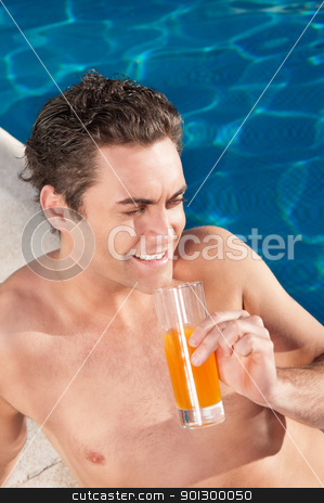 Handsome man by the poolside stock photo, Handsome man by the poolside with a glass of orange juice by Tyler Olson