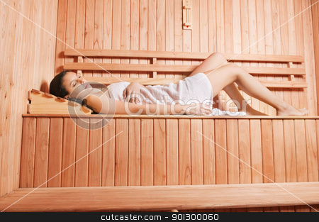 Young woman enjoying sauna stock photo, Beautiful young woman laying in sauna with eyes closed by Tyler Olson