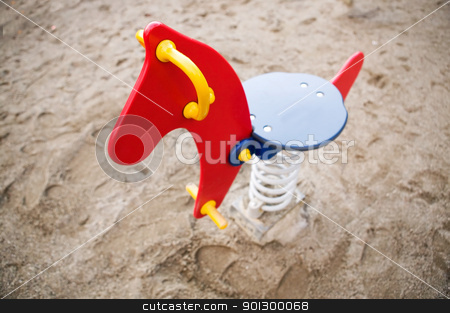 Playground Rocking Horse stock photo, A brightly colored red, blue and yellow rocking horse in a public playground surrounded by sand. - focus on the head with a shallow depth of field. by Tyler Olson