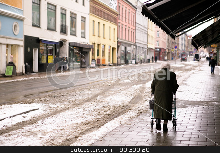 Old Woman with Walker stock photo, An old woman walking outdoors in the winter with a few snow crystals visible in the air. - Focus is on the woman with the background thrown out of focus. by Tyler Olson