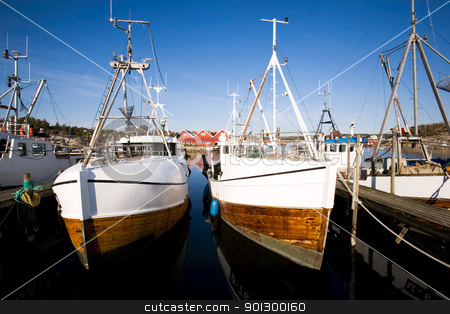 Fishing Boats at Dock stock photo, A number of fishing boats sit at dock on a warm summer day. by Tyler Olson