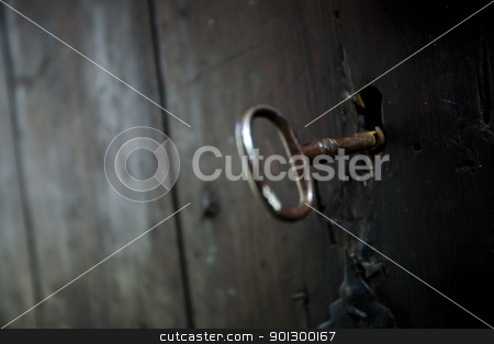 Skeleton Key stock photo, A skeleton key in a black door and lock.  Shallow depth of field with focus on key hole by Tyler Olson
