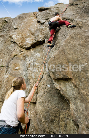 Two climbers stock photo, A female belaying a male on a steep rock face.  Shallow depth of field with the focus on the climbing which is belaying (the on at the bottom) by Tyler Olson