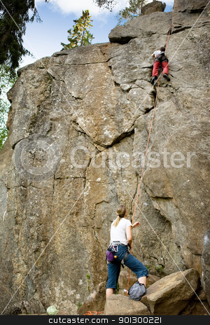 Two climbers stock photo, A female belaying a male on a steep rock face. by Tyler Olson
