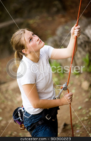 Female Belayer stock photo, A female belaying a male on a steep rock face.  Shallow depth of field has been used to isolated the belayer, with focus on the eyes and head. by Tyler Olson