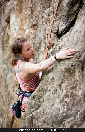 Female Climber stock photo, A female climber, climbing using a top rope on a steep rock face (crag).  A shallow depth of field has been used to isolated the climber, with the focus on the head and eyes. by Tyler Olson