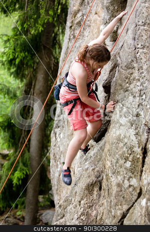 Female Climber stock photo, A female climber, climbing using a top rope on a steep rock face (crag).  A shallow depth of field has been used to isolated the climber, with the focus on the head and right hand. by Tyler Olson
