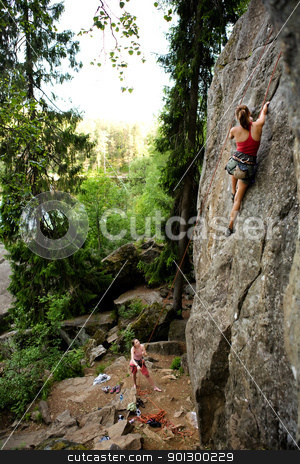 Two climbers stock photo, A female climber, climbing using a top rope on a steep rock face (crag) by Tyler Olson