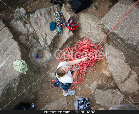 Female Belayer stock photo, A female climber belaying - viewed from above.  A shallow depth of field is used to isolate the climber - with focus on the eyes and head. by Tyler Olson