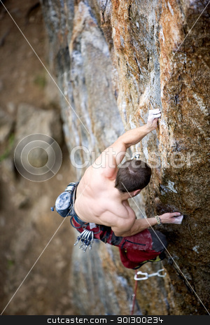 Male Rock Climber stock photo, A male climber, viewed from above, climbs a very high and steep crag. Shallow depth of field is used to isolate the climber with focus on the hands and head by Tyler Olson