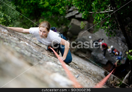 Female Climber stock photo, A female climber on a steep rock face.  Shallow depth of field is used to isolated the climber.  Focus is on the head, shoulders and arms of the climber. by Tyler Olson