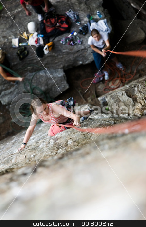 Female Climber stock photo, A female climber on a steep rock face viewed from above with the belayer in the background.  Shallow depth of field is used to isolated the climber. by Tyler Olson