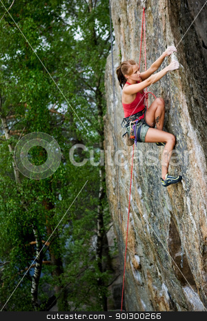 Female Climber stock photo, An eager female climber on a steep rock face looks for the next hold. Shallow depth of field is used to isolated the climber with the focus on the head. by Tyler Olson
