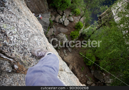 Step out on a Ledge stock photo, A foot on a ledge of a very high rock face by Tyler Olson