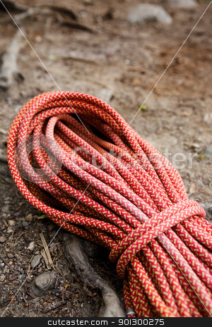 Climbing Rope stock photo, A climbing long orange climbing rope coiled up and placed on the ground.  The image has shallow depth of field. by Tyler Olson