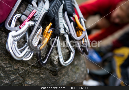 Quickdraws stock photo, A pile of quick draw carabiners with climbers out of focus in the background. by Tyler Olson
