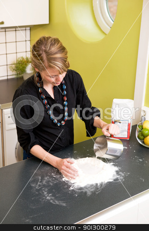 Woman Kneading Dough at Home stock photo, A young woman makes bread on the counter at home in the kitchen. by Tyler Olson