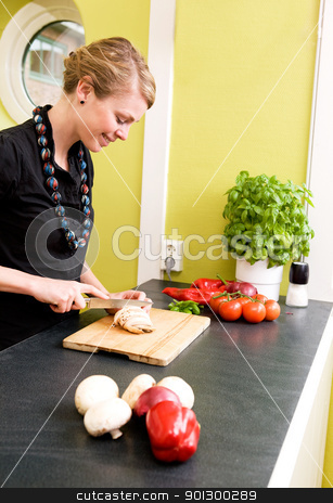 Slicing Vegetables stock photo, A woman cutting vegetables at home on the counter by Tyler Olson