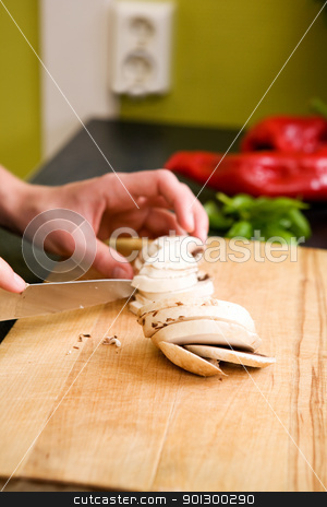 Female Slicing Mushrooms stock photo, A detail image of a female hand slicing mushrooms for a pizza.  Shallow depth of field is used, with focus on the hands and mushrooms. by Tyler Olson