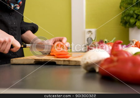 Cutting Tomatoes Detail stock photo, A detail image of a woman slicing tomatoes on a cutting board at home. - shallow depth of field with the focus on the tomato and knife by Tyler Olson