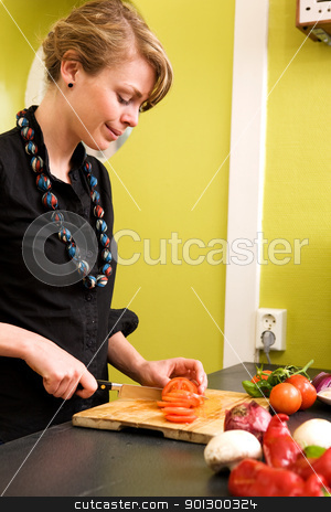 Slicing Tomatoes stock photo, A female is at home in the kitchen slicing tomatoes for a pizza. by Tyler Olson