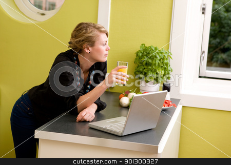 In Kitchen with Laptop stock photo, A woman using a laptop in the kitchen - looking out the window as though she is thinking about someone or something. by Tyler Olson