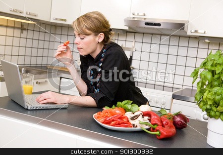 Surfing in the Kitchen stock photo, A young business woman surfs the internet while eating a healthy lunch of vegetables. by Tyler Olson