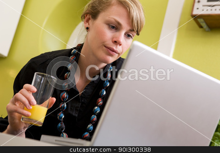 Online at Home stock photo, A young woman uses the computer in the kitchen while enjoying a glass of juice. The model is looking at the computer. by Tyler Olson