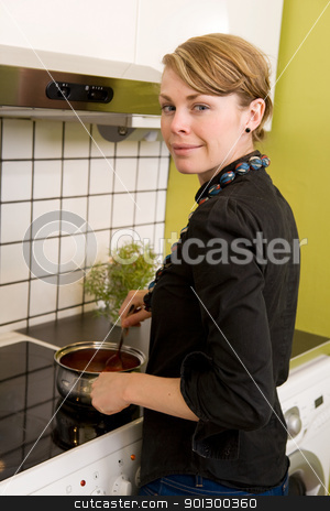 Cooking on the Stove stock photo, A female looking at the camera and smiling while cooking at home in her apartment. by Tyler Olson