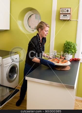 Fresh Pizza stock photo, A young woman takes a fresh pizza out of the oven in her apartment kitchen. by Tyler Olson