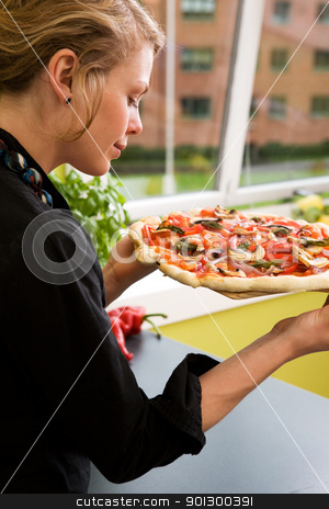 Young Woman with Fresh Pizza stock photo, A young woman presents a homemade italian style pizza fresh from the oven in her apartment kitchen. by Tyler Olson