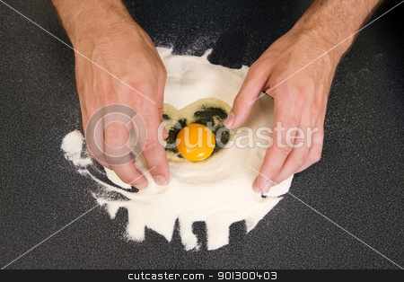 Making Pasta - Egg and Flour stock photo, A young man making pasta at home in an apartment kitchen.  An above view of an egg in flour ready to be mixed by hand. by Tyler Olson